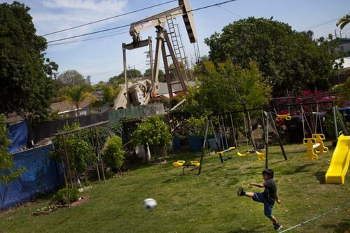 A child plays in a playground right next to an oil well in California. Photo courtesy of VISION.